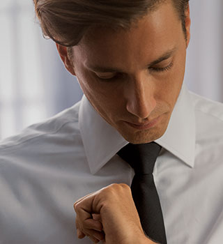A man who received BOTOX® Cosmetic ties his tie