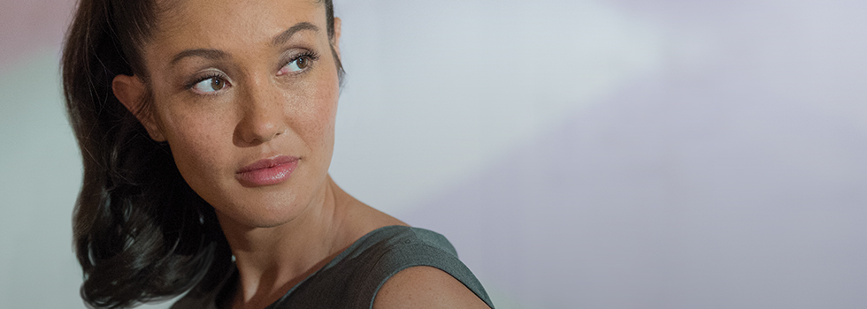 A woman who received BOTOX® Cosmetic looks over her shoulder